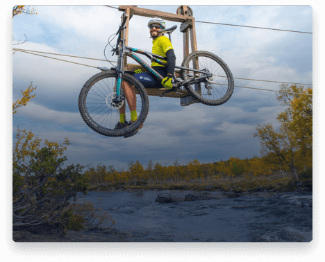 iFit Trainer Casey Zaugg riding a bike lift over a river in Norway.