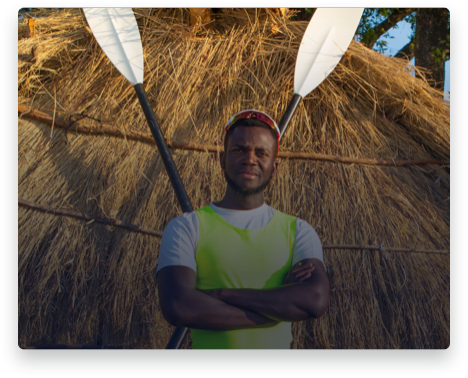 iFit Trainer Desmond Nanchengwa standing with his rowing oars in Zambia.