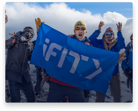 iFit Trainer Jake Norton standing with an iFit flag on Mount Kilimanjaro.