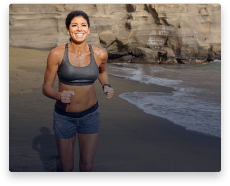 iFit Trainer Stacie Clark running on a beach in Hawaii.
