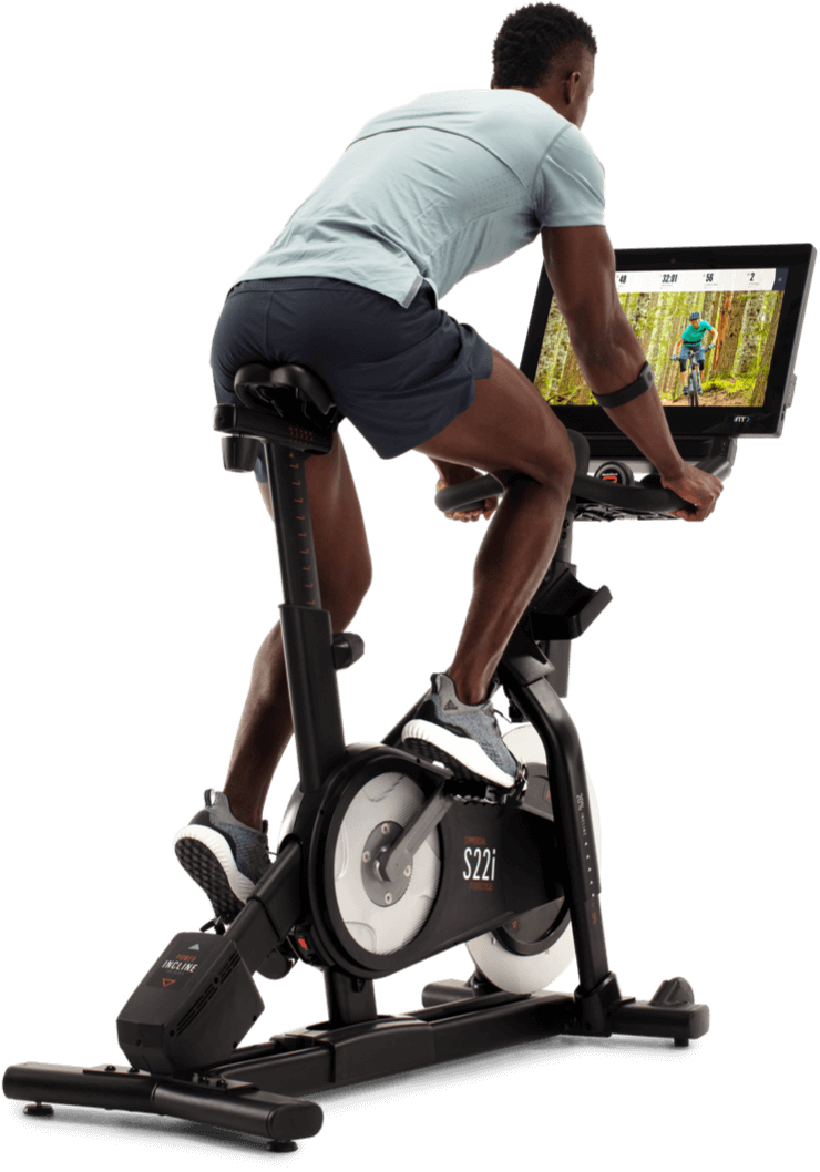 Man exercising on an iFit-enabled stationary bicycle.