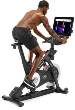 A man exercising on a stationary bicycle.